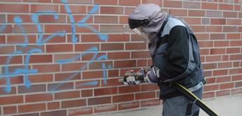 Mit einem speziellem Sandstrahlverfahren reinigen wir Untergründe schonend & entfernen Graffitis oder Beschmutzungen.